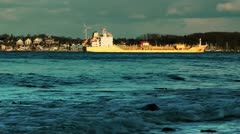 Rolling waves and cargo ship on coastline of Laboe, Kiel, Germany, panning - stock footage