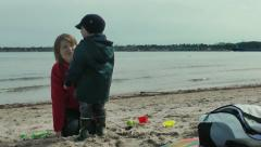 Mother and little boy on the beach, cargo ship on the background Stock Footage