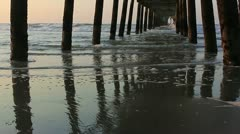Sea and surf  under fishing pier at dawn Stock Footage