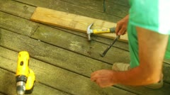 Prying nails nail board wood deck Stock Footage