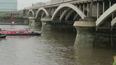 Canal Boats / Narrowboats pass under a bridge on the River Thames Stock Footage