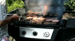 Cooking a lot of hamburgers on a gas grill Stock Footage
