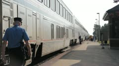 Stock Footage - A Conductor walks the length of train as passengers load luggage Stock Footage