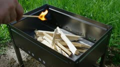 Making fire wood .lighting BBQ wood with match. Stock Footage