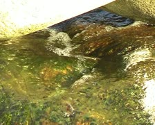 Water trickles gently through two rocks light reflecting SD - stock footage