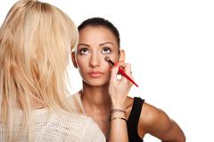 Makeup artist applying makeup to her model Stock Photos