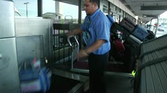 LAX Airline worker puts luggage on belt 0021TE Stock Footage