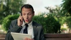 Angry businessman with cellphone and documents in the park, dolly shot HD Stock Footage