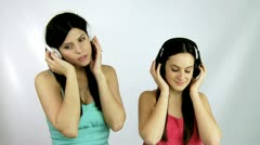 Female models listen to slow music with headphones medium shot Stock Footage