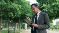 Young businessman working on tablet computer in the park, dolly shot HD Stock Footage