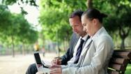 Business couple with laptop and documents in park, dolly shot HD Stock Footage
