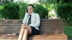 Attractive businesswoman talking on cellphone in the park, dolly shot HD - stock footage
