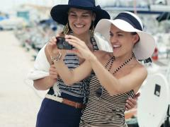 Glamour friends taking picture of themselves with cellphone, steadicam shot NTSC - stock footage