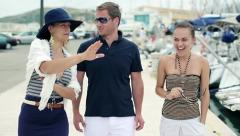 Young rich friends walking and talking in marina, steadicam shot HD - stock footage