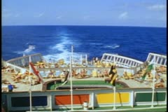 QE2 stern, 1982 World Cruise, sea in retreat, busy stern deck, people, sunny - stock footage