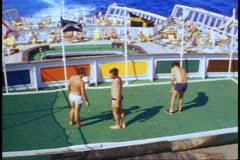 QE2 deck, 1982 World Cruise, young men on deck, putting green, sea in background - stock footage