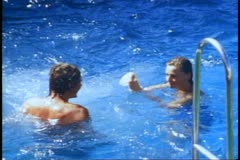 QE2 deck, 1982 World Cruise, medium shot of couple swimming in pool Stock Footage