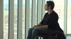 Stock Video Footage of Man in wheelchair looking out a highrise window