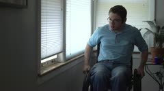 Man in wheelchair looking out window at home Stock Footage