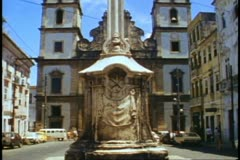 Salvador, Brazil, giant cross in foreground, church, tilt up, medium wide shot Stock Footage