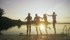WS Friends jumping off jetty into lake Stock Footage