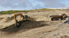 Excavator Loads Dirt into Backing Dump Truck Stock Footage