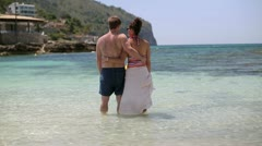 Young couple standing in the sea and looking at the bay Stock Footage