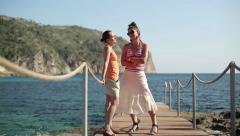 Happy female friends talking on pier, dolly shot Stock Footage
