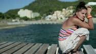 Sad woman squatting on pier, dolly shot Stock Footage