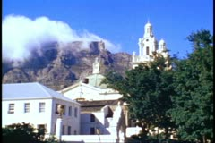 Table Mountain, clouds atop, medium shot, colonial buildings foreground Stock Footage