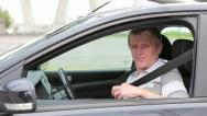 Senior male sitting in car and fastens seat belt Stock Footage
