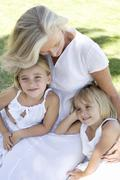 Grandmother cuddling her granddaughters Stock Photos