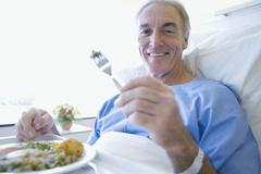 Senior patient eating a hospital meal Stock Photos