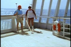 QE2 1982 World Cruise, Shuffleboard on deck, two men, medium wide shot Stock Footage