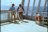 Stock Video Footage of QE2 1982 World Cruise, Shuffleboard on deck, two men, medium wide shot
