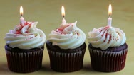 Three chocolate cupcakes with a white candle in each Stock Footage