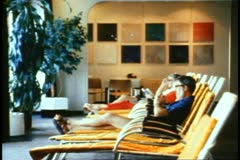QE2, 1982 World Cruise, interior deck chairs, people seated, relaxing - stock footage