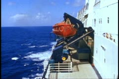 QE2, 1982 World Cruise, side shot from bridge wing, red lifeboats, sea passing Stock Footage