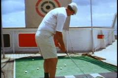 QE2 1982 World Cruise, Golf driving blind, man swings, medium shot Stock Footage