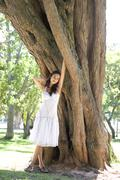 Woman leaning against a tree Stock Photos