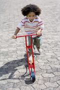Boy riding a toy scooter Stock Photos