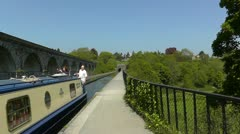 Canal boat on Llangollen canal at Chirk aqueduct, Wales Stock Footage