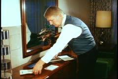 Cabin steward making up cabin, medium shot, at desk laying out papers Stock Footage