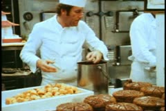 QE2 galley, chef dunks balls in chocolate, places on cake, medium shot - stock footage
