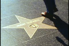 Hollywood Walk of Fame, feet crossing star, Jimmy Durante's star, close up Stock Footage