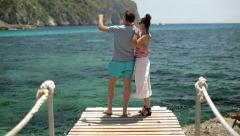 Young couple standing on pier by the sea and looking at something Stock Footage