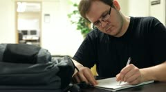 Male student taking notes in notebook Stock Footage