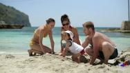Happy family playing in sand on the beach Stock Footage