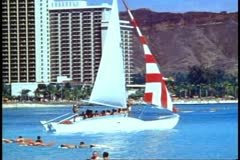Waikiki, sailboat sailing out to sea past Diamond Head, medium shot Stock Footage