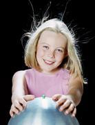 Girl using van de graaff generator Stock Photos